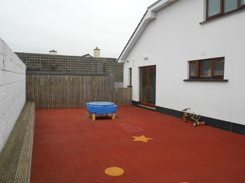 Enclosed outside playarea with coloured safety surface covering. Walled in and gated waste and facilitiy equipemnt storage. Seating area from treated deck boards incorporated onto the external boundary wall. Work carried out by Eugene Foley Construction Limited.