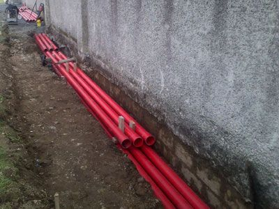 Extensive set of ducting pipes being laid beside a boundary wall of a commercial premises on a busy road by the team at Eugene Foley Construction Limited.